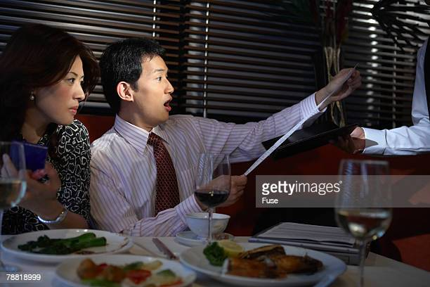 Shocked Businessman Reading Bill at Restaurant