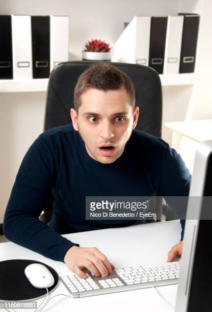 shocked businessman using computer at desk in office - benedetto photos et images de collection