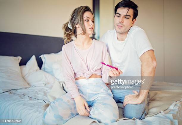 shocked couple is looking positive pregnancy test in the bedroom - human fertility stock pictures, royalty-free photos & images