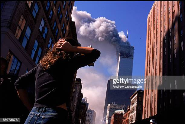 Shocked crowds of downtown Manhattanites observe the burning World Trade Center towers in New York City early September 11, 2001. Three hijacked...