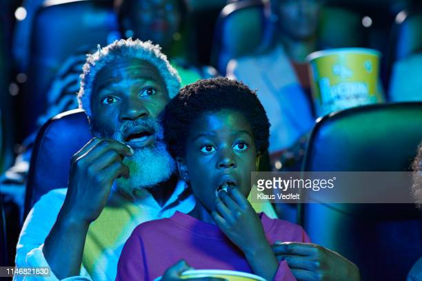 shocked father and daughter eating popcorn while watching horror movie in theater - between two ferns: the movie stock pictures, royalty-free photos & images