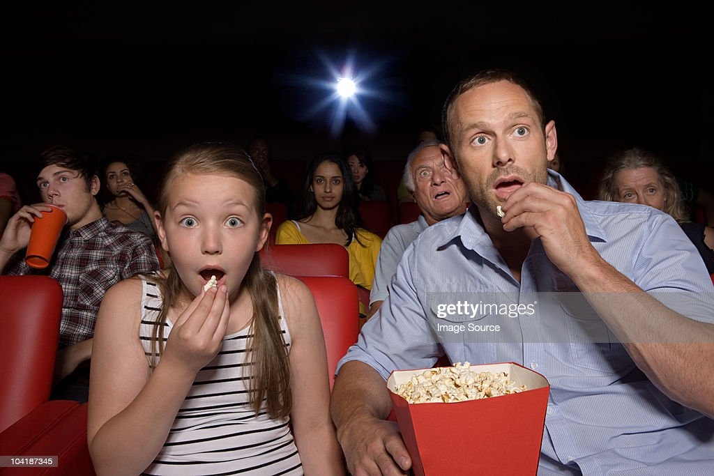 Shocked father and daughter in movie theater : Stock Photo
