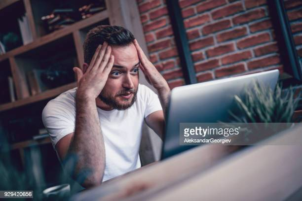 shocked freelancer in disbelief working at his favorite coffee place - shock stock pictures, royalty-free photos & images