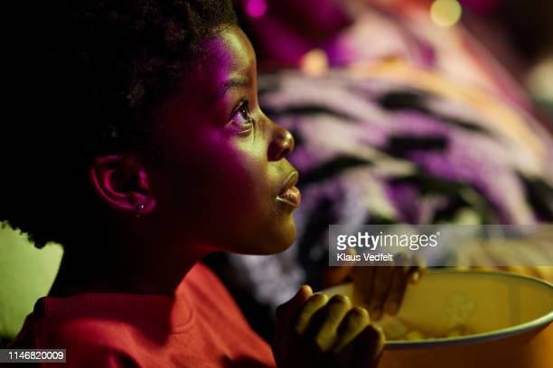 shocked girl watching thriller movie in cinema hall at theater - color out of space 2019 film stockfoto's en -beelden