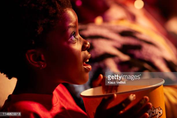 shocked girl with popcorn watching thriller movie in cinema hall at theater - film industry stock pictures, royalty-free photos & images