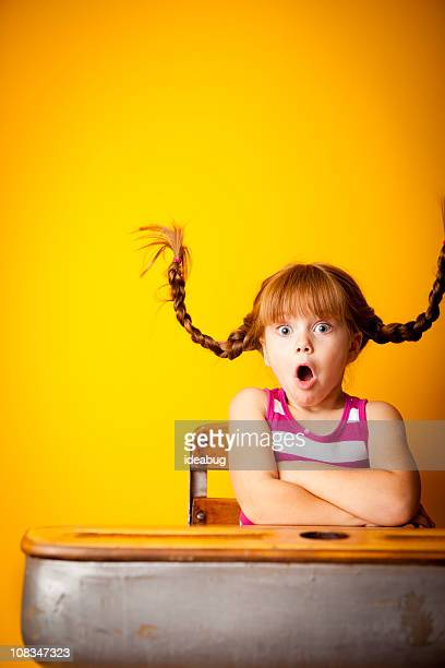 Schockiert Mädchen mit nach oben, geflochtener Zopf sitzen auf Schule-Schreibtisch