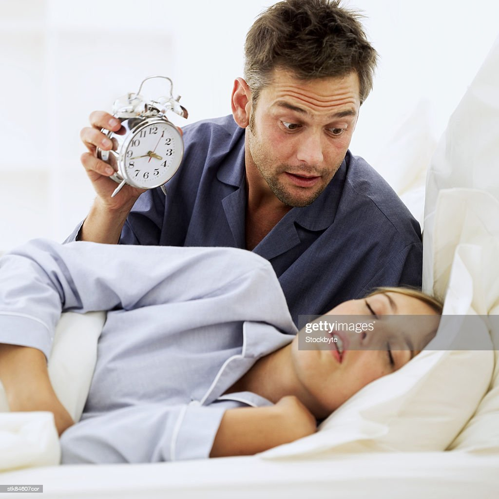 shocked man holding an alarm clock and looking at his wife : Stock Photo