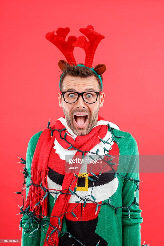 Shocked man in funny winter outfit against red background : Stockfoto