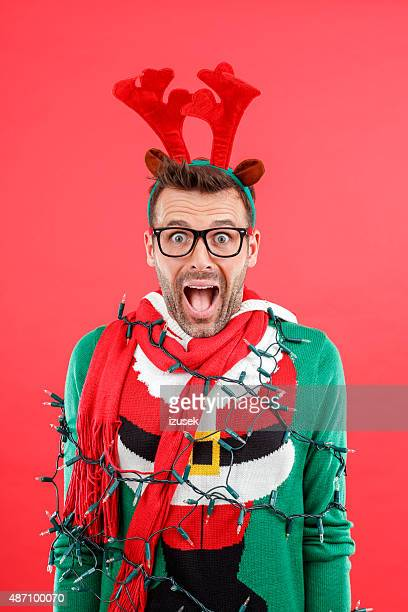 Shocked man in funny winter outfit against red background