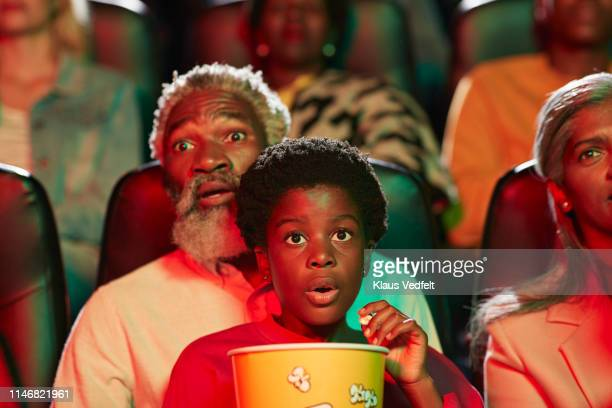 shocked man watching horror movie with girl in cinema hall - color out of space 2019 film stockfoto's en -beelden
