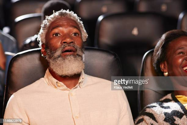 shocked man watching movie by smiling woman in cinema hall at theater - horror movie stock pictures, royalty-free photos & images