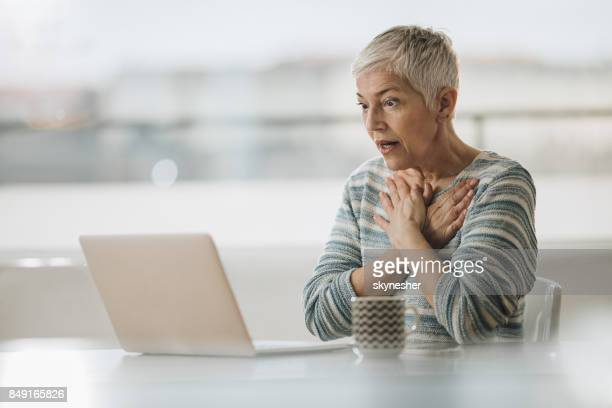 Shocked mature woman reading an e-mail on laptop.