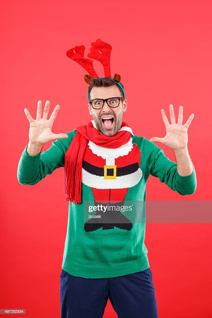 Shocked nerd man in funny winter outfit against red background : Stock Photo