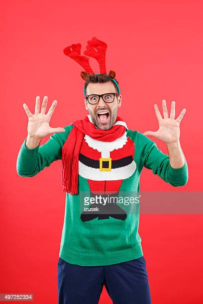 shocked nerd man in funny winter outfit against red background - santa face stockfoto's en -beelden