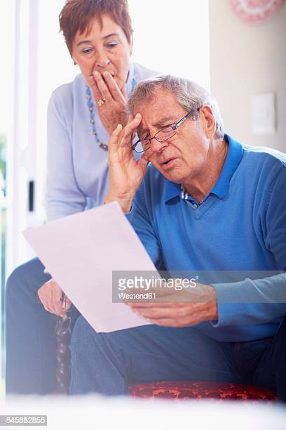 Shocked senior couple reading document at home