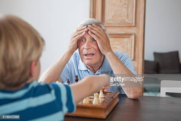 shocked senior man with head in hands looking at grandson while playing chess at home - defeat stock pictures, royalty-free photos & images