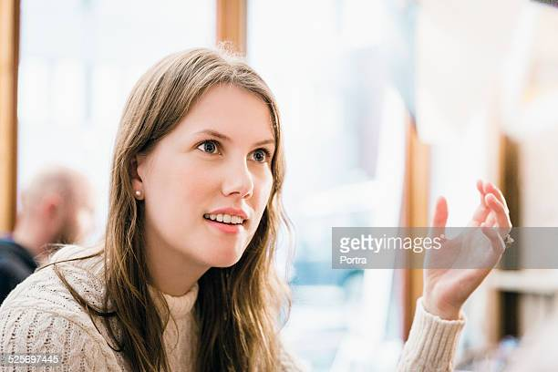 Shocked woman gesturing at restaurant