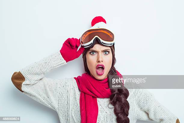 Shocked woman in winter outfit, wearing woolen cap and goggle