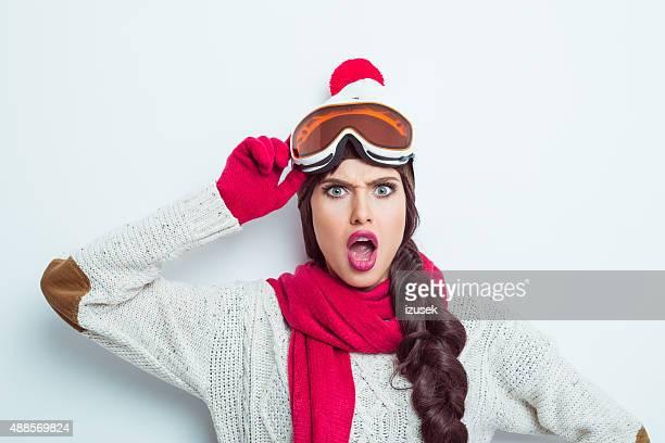 Schockiert Frau in winter-outfit, Mütze und Brille tragen woolen