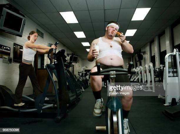 shocked woman looking at fat man eating donut while exercising in gym - fat people eating donuts stock pictures, royalty-free photos & images