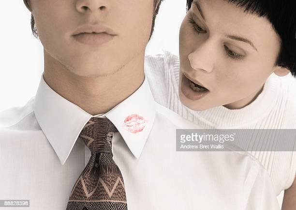 Shocked woman looking at lipstick on shirt of man