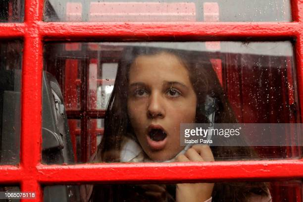 shocked woman receiving news on the phone - telephone booth stock pictures, royalty-free photos & images