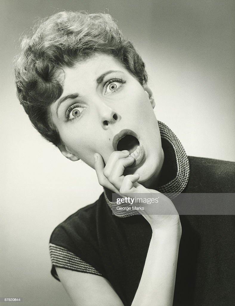 Shocked woman with fingers on lips in studio, (B&W), portrait : Stock Photo