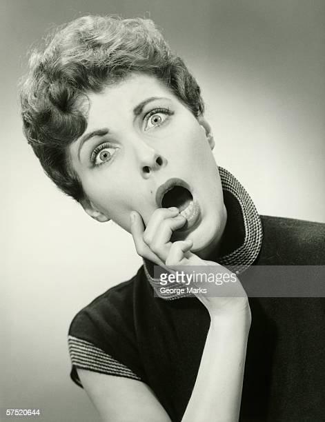 Shocked woman with fingers on lips in studio, (B&W), portrait