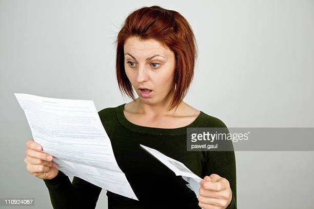 Shocked woman with wide open mouth receives credit card statement
