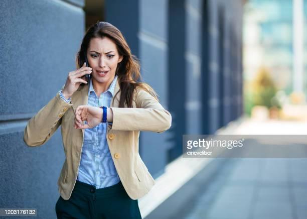 geschokte jonge onderneemster die tijd op polshorloge controleert terwijl het spreken mobiele telefoon - polshorloge stockfoto's en -beelden