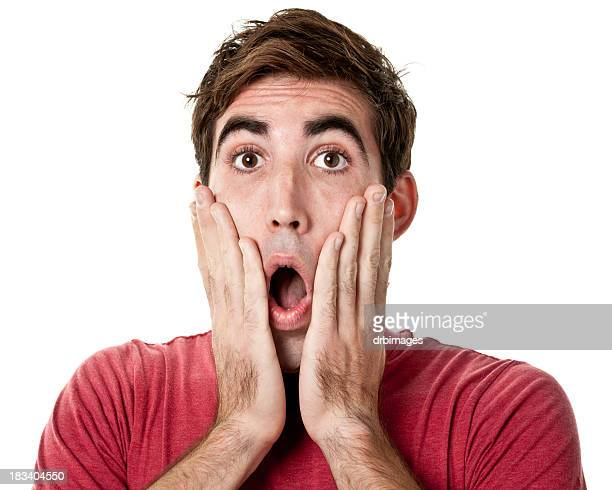 shocked young man with hands on cheeks - scary face stock photos and pictures