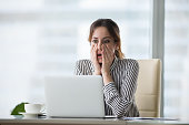 Shocked young woman looking at laptop screen.