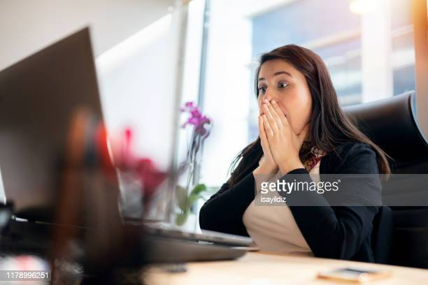 shocked young woman looking at laptop screen - achievement stock pictures, royalty-free photos & images
