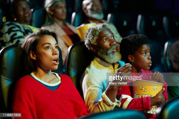 shocked young woman watching horror movie by audience in theater - film industry stock pictures, royalty-free photos & images
