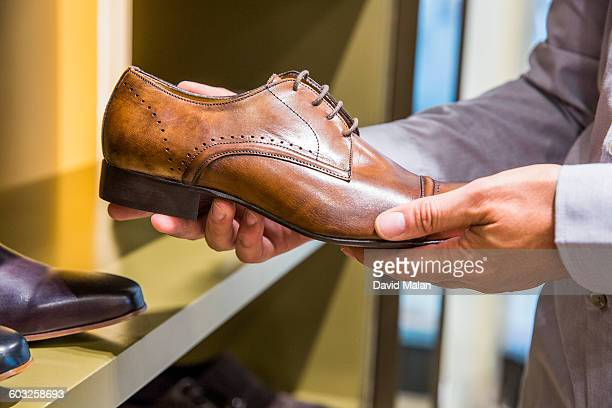 shoe being looked at in an upmarket store. - leather shoe stock pictures, royalty-free photos & images