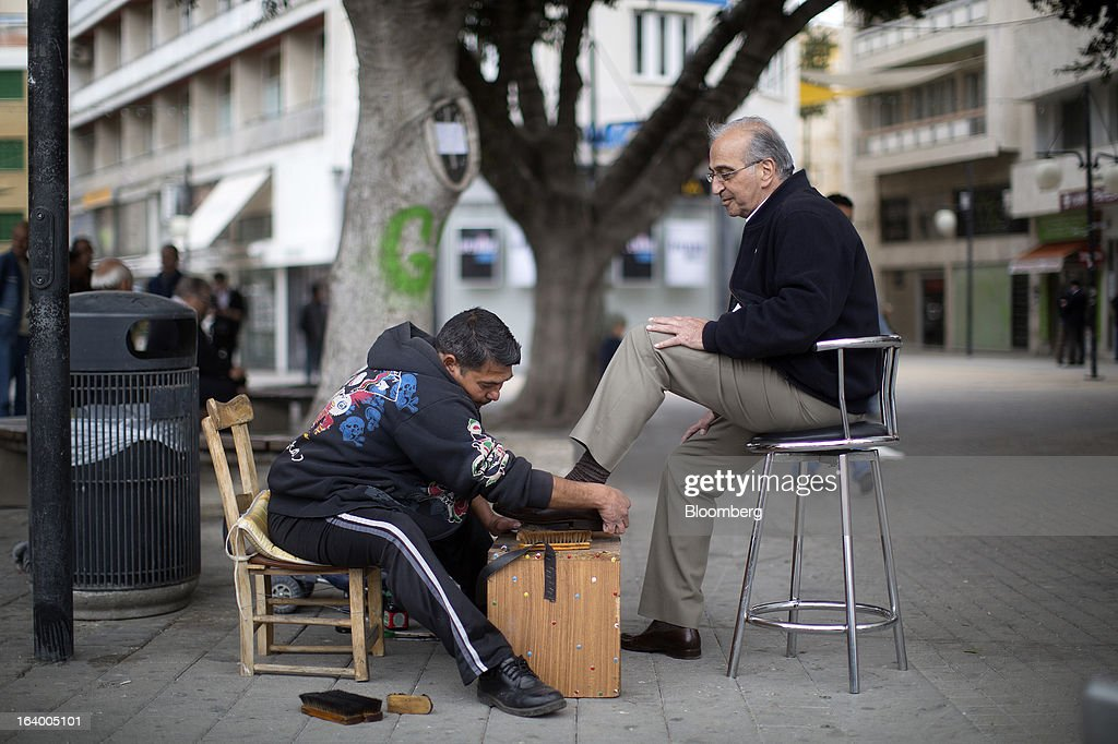 A shoe cleaner polishes a man's shoes on a street in central Nicosia, Cyprus, on Tuesday, March 19, 2013. Euro-area finance ministers told Cyprus to raise 5.8 billion euros ($7.5 billion) from bank depositors to unlock emergency loans, maintaining the revenue target while suggesting sparing small-scale savers. Photographer: Simon Dawson/Bloomberg via Getty Images