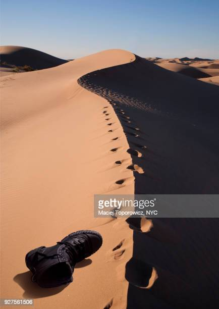 Shoe laying down on a sand desert next to human footprints.