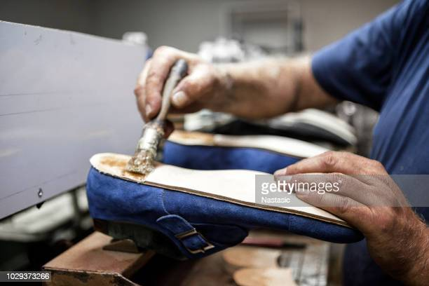 shoe maker holding brush ,gluing shoe - leather boot stock pictures, royalty-free photos & images