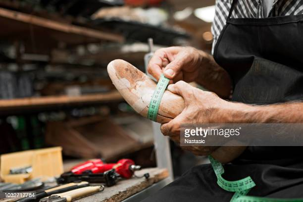 shoe maker with foot measure mold - tongs work tool stock photos and pictures