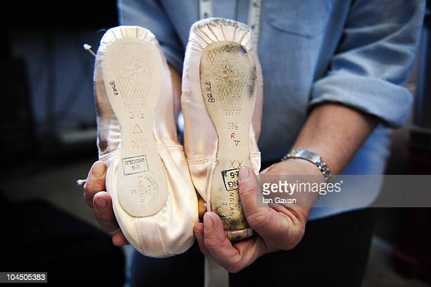 Shoe Mistress Julie Heggie of the English National Ballet compares an example of a worn out brand new and worn in pointe shoe in her office at...