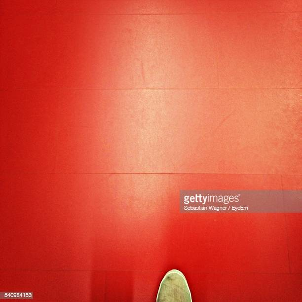 shoe on red floor - lino stock pictures, royalty-free photos & images