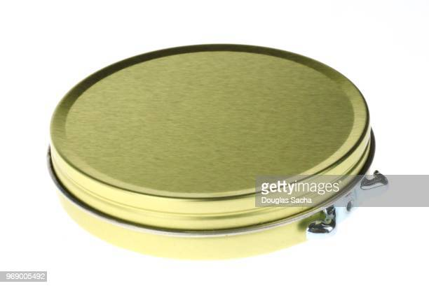 Shoe polish tin with a side-mounted twist knob for opening on a white background