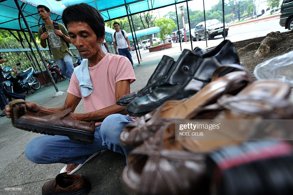 Shoe polisher Eddie Aguilar, 63yrs old, brushes a shoe and earns an average of six USD a day on a street of Manila on June 16, 2010. The Philippines' jobless rate rose to a near four-year high of 8 percent in April despite the economy growing quickly, official data showed. The impoverished Philippines, with a total population of more than 90 million people, also has a huge pool of unskilled people with scant education who hold temporary jobs outside the official labour market.