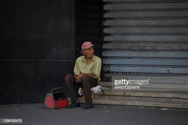 A shoe polisher sits waiting for customers as people have opted to comply with the government issued curfew on April 2 2020 in San Salvador El...