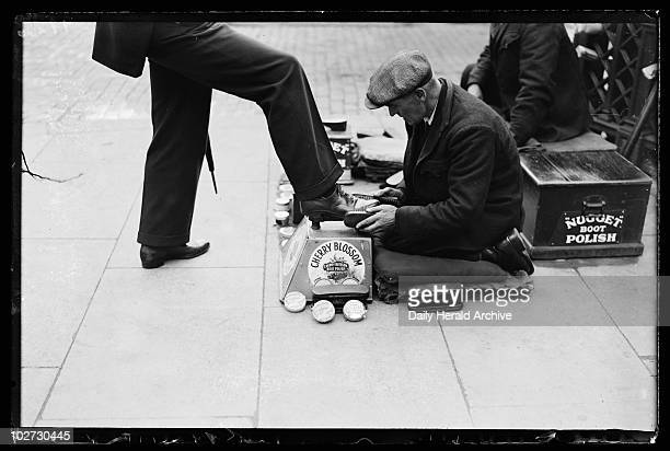 Shoe polishing 1932 A photograph of a man kneeling to polish someone's shoes taken by Woodbine for the Daily Herald newspaper on 12 October 1932 The...