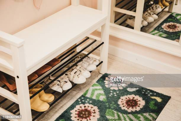 shoe rack with different size shoes showing the concept of family - rack stock pictures, royalty-free photos & images