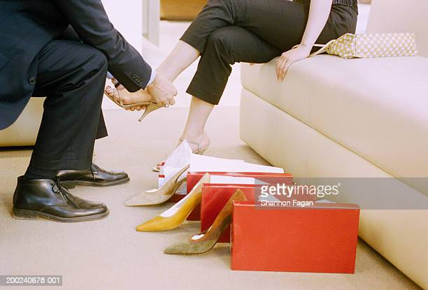 shoe salesman assisting woman in shop, low section, side view - scarpe foto e immagini stock