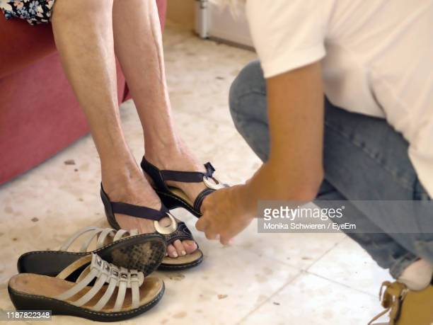 shoe salesman assisting woman in shop - open toe stock pictures, royalty-free photos & images
