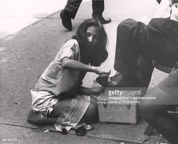 A shoe shine girl working shining a man's shoes on the sidewalk New York ca1950s Photo by Weegee /International Center of Photography/Getty Images