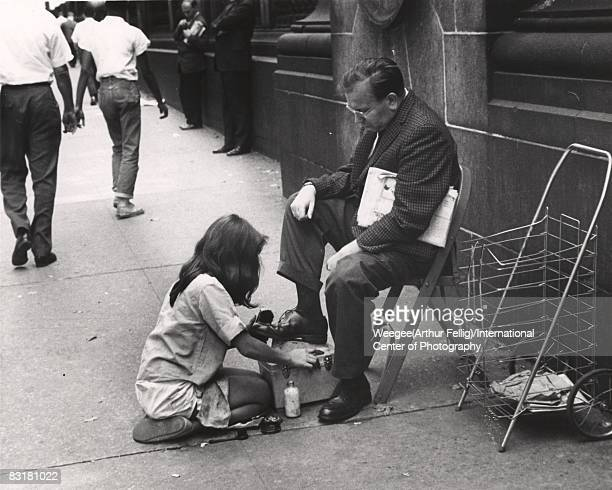 A shoe shine girl working shining a man's shoes on the sidewalk the man is sitting on a folding chair and holding a newspaper New York ca1950s Photo...